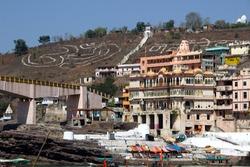 View of mountain Ohm and writing Ohm Namah Shavaya, river Narmada, bridge and buidings at Onkareshwar, Madhya Pradesh, India, Asia