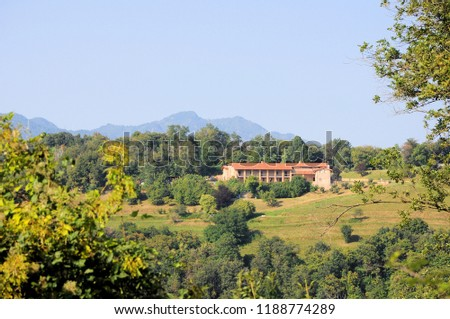 View of mountain with woods and old isolated farmhouse.