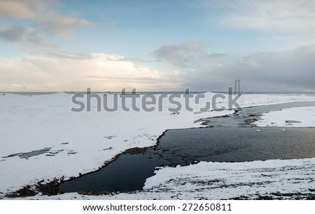 View of mountains, snow covered plains and rivers in southern Iceland during winter.