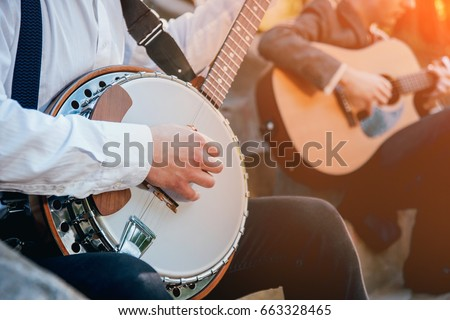 View of musician playing banjo at the street - Shutterstock ID 663328465