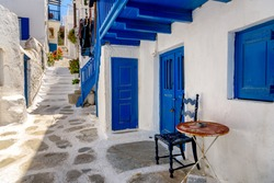 View of Mykonos island white and blue traditional building on a narrow alley.
