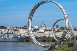 View of Nantes,France.Nantes panorama across Loire River.The Buren metal rings decoration. Sightseeing on Ile de Nantes.Beautiful European cityscape. French urban architecture