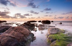 view of Natural coastal rocks with waves trails during sunset. image contain soft focus and blur due to slow shutter.