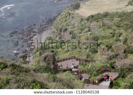 View of nature trail with tourists from Seongsan Ilchulbong (Sunrise Peak)  during spring time in Jeju Island,South Korea. This inactive volcano is one of the UNESCO nature tourism site.