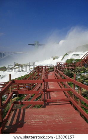 View of Niagara Falls (American side) from the base below, at the bottom of the waterfall. This view shows the walkway at the bottom of the Bridal Veil, the observation tower and the Rainbow bridge