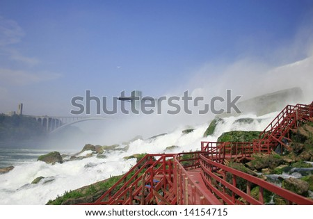 View of Niagara Falls (American side) from the base below, at the bottom of the waterfall: walkway at the bottom of the Bridal Veil and  observation tower and the Rainbow bridge