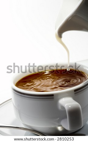 View of nice fresh milk stream flowing down in to the cup of coffee