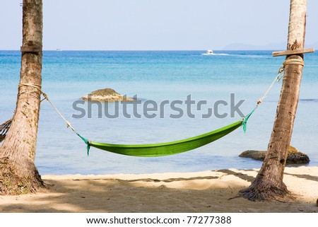 View of nice tropical empty sand beach with some palm and hammock . Thailand .