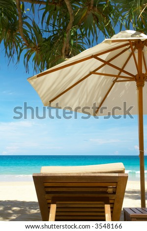 view of nice umbrella  and  teakwood chair on tropic beach