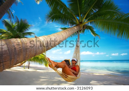 view of nice woman reading a book in hammock in tropical environment