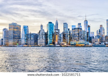 View of NYC New York City downtown lower financial district skyscrapers, east river, cityscape skyline during evening sunset, dusk, twilight