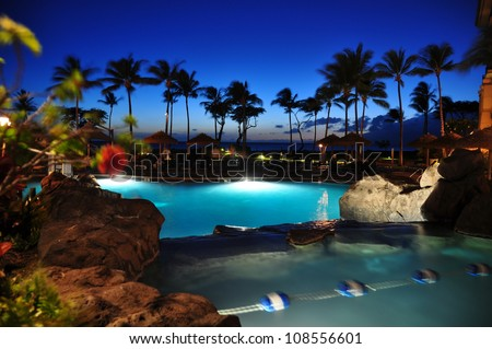 View of ocean from luxury hotel at night, Kaanapali, Maui, Hawaii with palm trees.