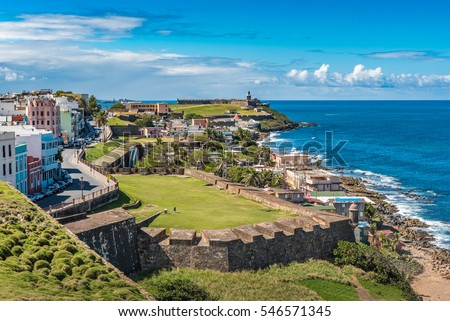 View of ocean towards San Felipe del Morro from Castillo de San Cristobal with castle wall and grass fields in between