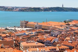 View of old city of Lisbon with red roofs and bridge in the background, Portugal