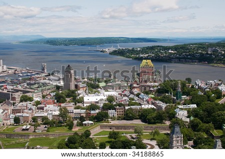 View of old city of Quebec with the St. Lawrence river and Orleans in background and city wall in foreground.  Chateau Frontenac landmark can be seen
