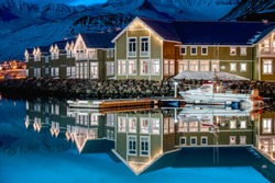 View of old harbour in Siglufjordur, fishing village surrounded by snowy mountains, winter season in Iceland