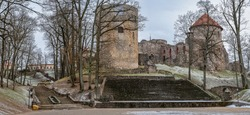 View of old medieval castle and old stone stairs in city park in Cesis, Latvia. Cesis Castle is one of the most iconic and best preserved medieval castles in Baltics