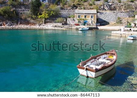 View of old stone house with a wooden boat moored in little bay