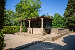 View of old structure with granite pillars and orange ceramic tile roof, with fountain in the interior and exterior tank, inserted in the Gardens of Solar de Mateus...