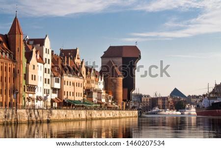 View of old town Gdansk (Gdańsk / Danzig), Poland (Polska / Polen) with merchants' houses, and historic medieval Crane (Żuraw / Krantor). Beautiful calm morning on the Motlava (Motława) River.