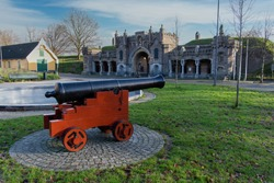 View of one of the entrance gates of the fortified town of Naarden, The Netherlands; one of the best preserved fortified towns in Europe and famous for its unique star shape; cannon in the front