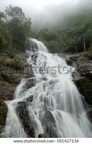 View of one section of the tall Thac Bac (Silver) Waterfall in Sapa, Vietnam, on a foggy day. #581427136