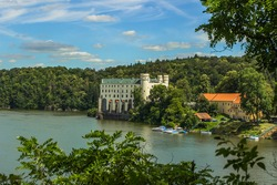 View of Orlik Castle, must see in the Czech Republic.Famous tourist place on a rock above Vltava river.Beautiful summer landscape with Orlík Water Reservoir and boats.Travel background space for text