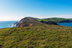 View of Pacific Ocean coastline, with winter green grass covering cliffs and bluffs of Point Reyes Headlands on a sunny day at Point Reyes National Seashore, California