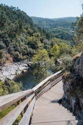 View of Paiva river, from wooden walkway, in Arouca geopark, Portugal. Blue water and green mountain landscape in the background.