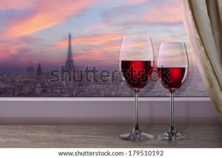 View of Paris and Eiffel tower on sunset from window with two glasses of wine