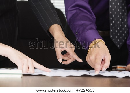 View of people pointing fingers on paper. - stock photo