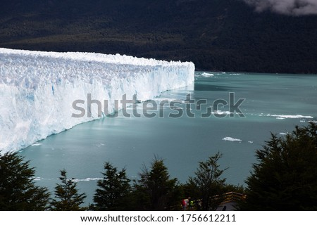 View of Perito Moreno glacier in Argentina with ice melting and floating in the water. Climate change and environmental emergency context. Travel context