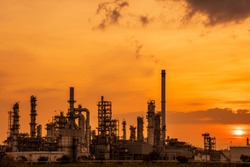 View of petrochemical plants and oil refineries, natural gas storage tanks, steel pipes behind the yellow sunrise