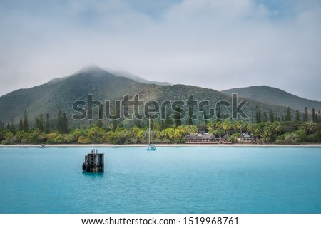 View of Pic N'Ga Mountain engulfed in clouds and the turquoise waters of Kuto Bay with a waterfront restaurant on its white sandy beach on Isle of Pines in New Caledonia Archipelago in South Pacific.