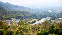View of picturesque haze valley of the Kok River and Thai border town of Tha Ton from the hill top close to Wat Tha Ton. The Mekong tributary flows through the highlands of Northern Thailand.