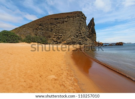 View of Pinnacle Rock and breaking waves from the red sand beach on Bartolome Island, Galapagos National Park, Ecuador, with Sullivan Bay, cruise ships, and Santiago Island in the background