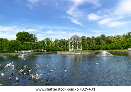 View of pond and blue sky against green trees of summer garden