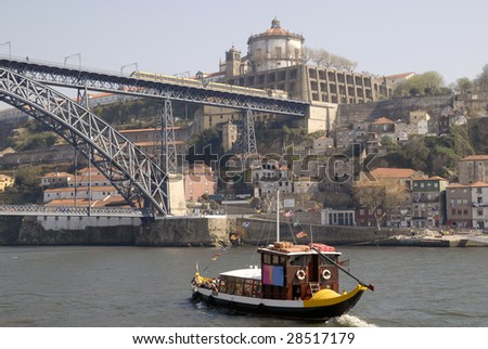 View of Porto city, Portugal. Porto city, excursion boat in the river Douro and the Bridge of Luis I with tram, Portugal.  It was made by design o? Gustaf Eiffel. Point og interest in Portugal.