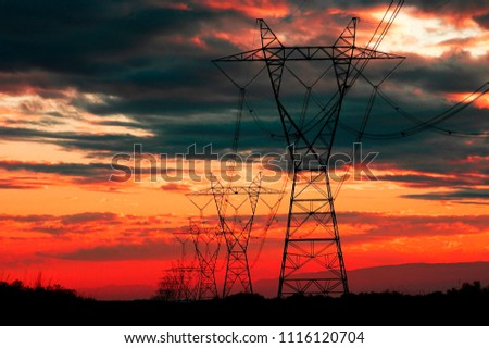 View of powerlines with sunset and clouds in background for communication and electricity #1116120704
