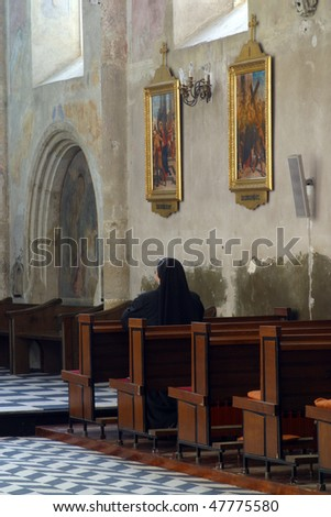 View of praying sister inside church