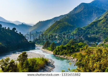 View of Ramganga river and the valley to the village and fields on the background of blue mountain ranges of the Himalayas, near Nainital, Uttarakhand, India.
