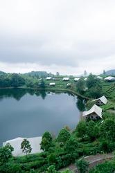 View of Rancabali lakeside Ciwidey Bandung West Java. Establishing shot from top, cloudy rainy sky, green tree, lake, and hills.