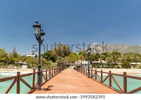 View of red wood bridge 'Embarcadero' in Marbella. View of Luxury area Puente Romano, expensive urbanisations. Mountain 'La Concha'. Spectacular travel destination. Emerald water, no people Foto stock ©