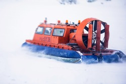 View of rescue team Hovercraft. hover craft transport boat crossing frozen river lake on the ice in the winter snowy day