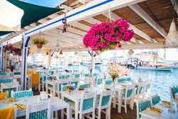 View of restaurant or cafe and bougainvillea flowers on beach in Gumusluk, Bodrum city of Turkey. Aegean seaside style colorful chairs, tables and flowers in Bodrum town near beautiful Aegean Sea.