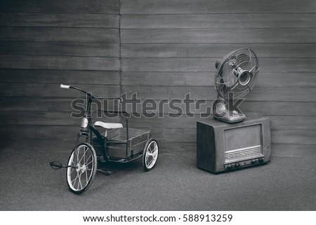 View of retro tricycle, retro fan, retro radio in the room. Black and white tone. #588913259