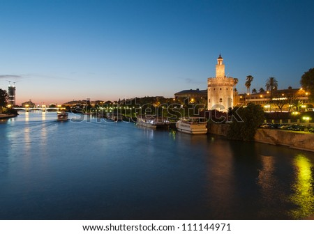 view of river Guadalquivir in Seville, Spain with Golden Tower (Torre del Oro) and Triana bridge at night