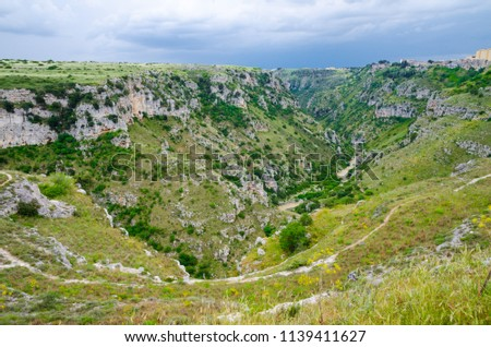 View of river valley with ravine canyon, rocks, green grass, path, caves di Murgia Timone and dark blue sky background near old ancient town Matera (Sassi), UNESCO Heritage, Basilicata, Southern Italy #1139411627