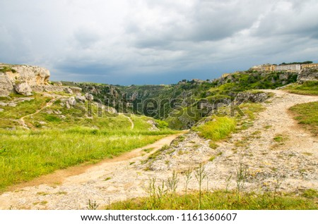 View of river valley with ravine canyon, rocks, green grass, path, caves di Murgia Timone and dark blue sky background near old ancient town Matera (Sassi), UNESCO Heritage, Basilicata, Southern Italy #1161360607
