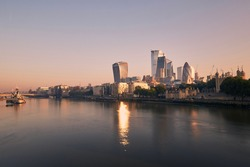 View of riverbank Thames River against skyscrapers. Urban skyline of London at morning light , United Kingdom.